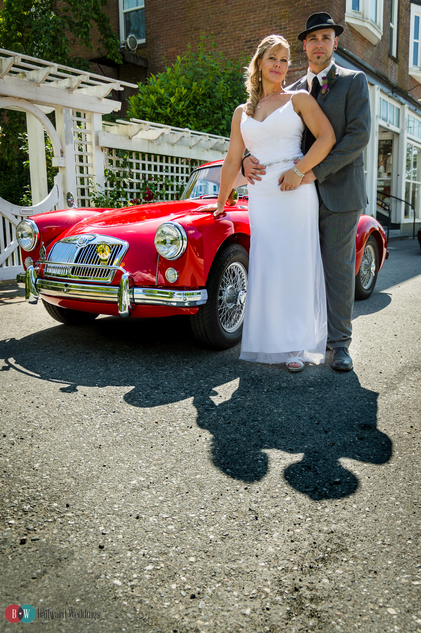 Bride and groom posing in front of classic car