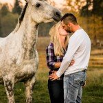 Engagement couple kissing by horse
