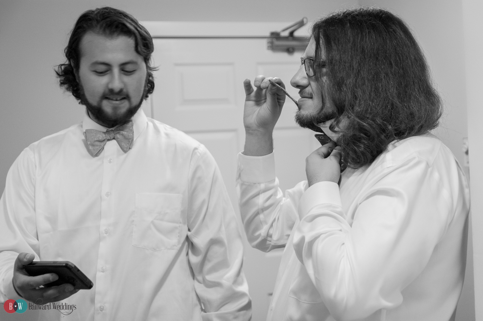 Groom and best man tying bow ties