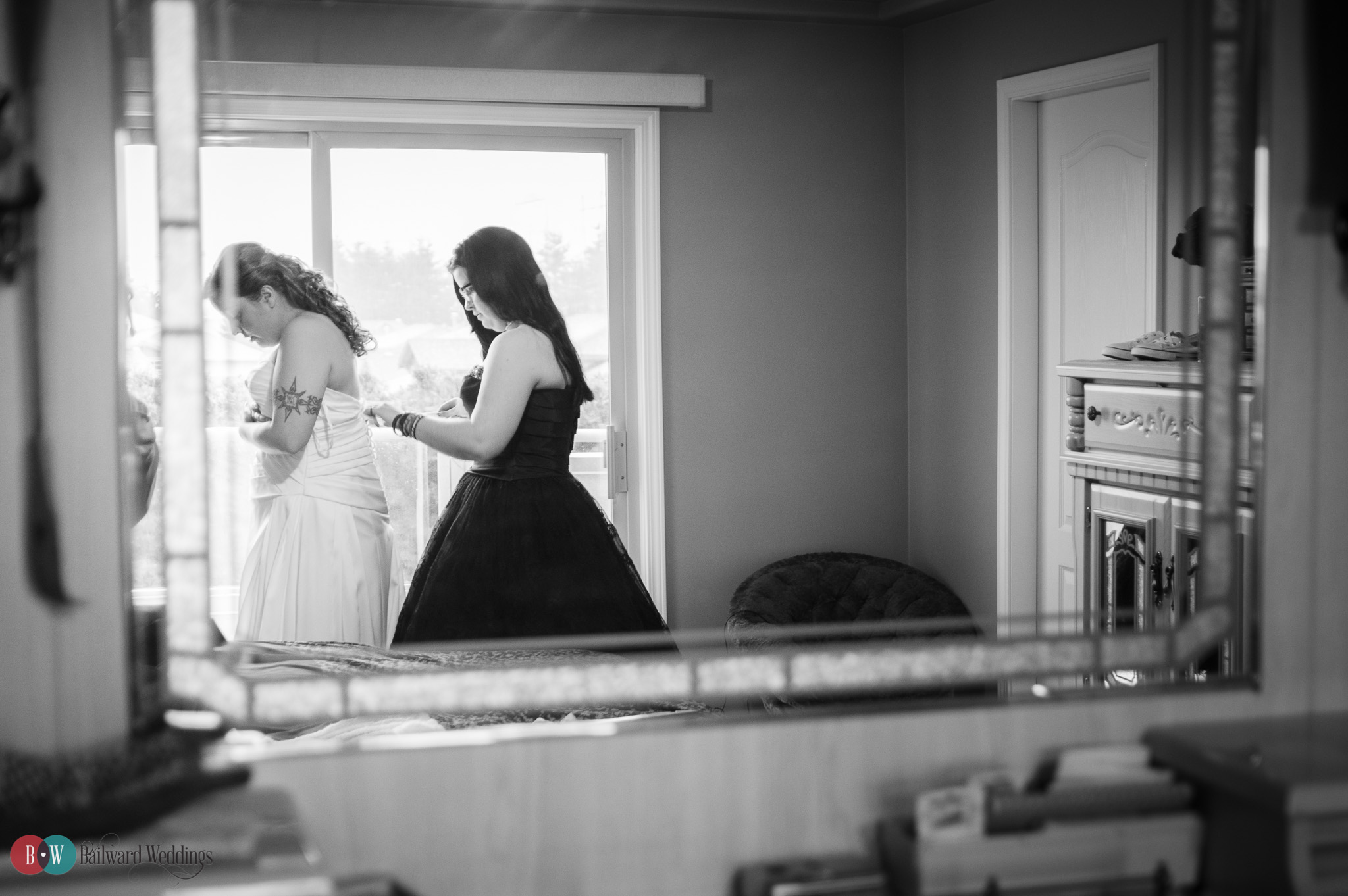 Bridesmaid getting bride ready in wedding dress