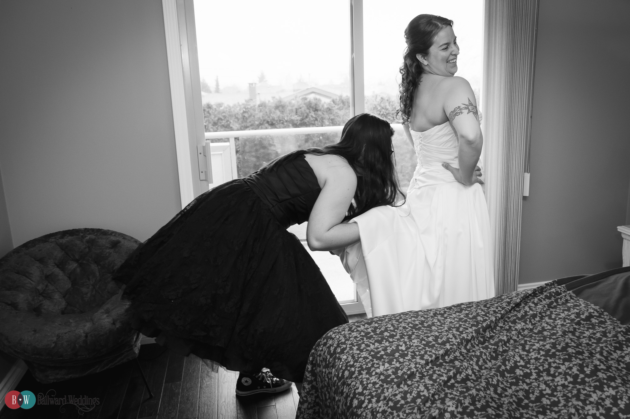 Bride and bridesmaid getting ready, bridesmaid's hand up dress
