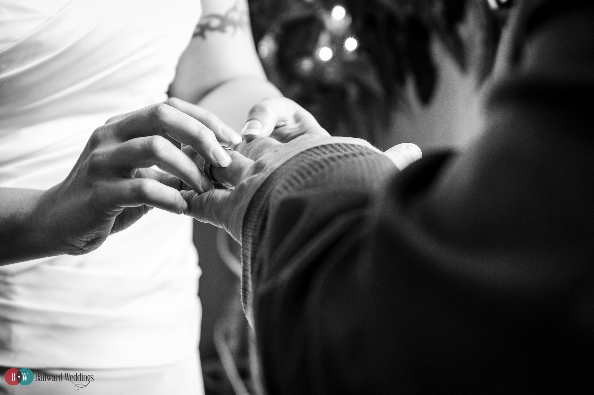 Bride putting ring on groom's hand