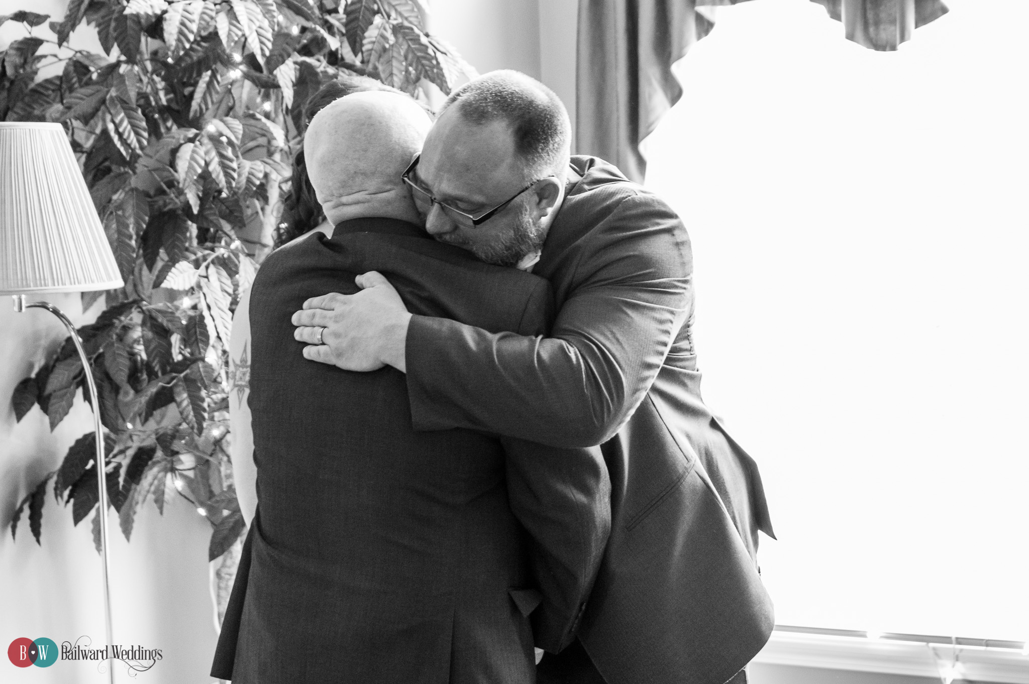 Father of the bride hugs groom