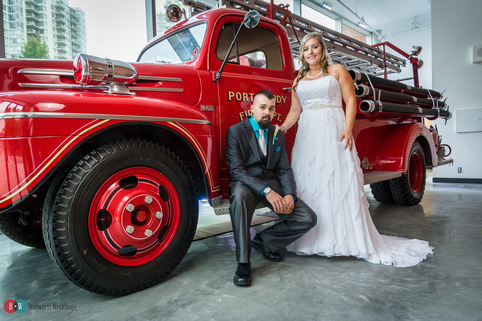Bride and Groom posing beside red fire truck