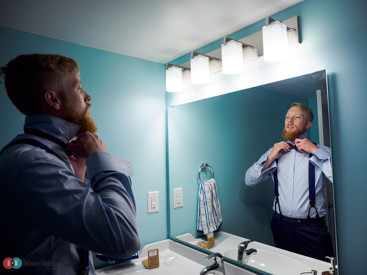 Groom tying tie in bathroom mirror