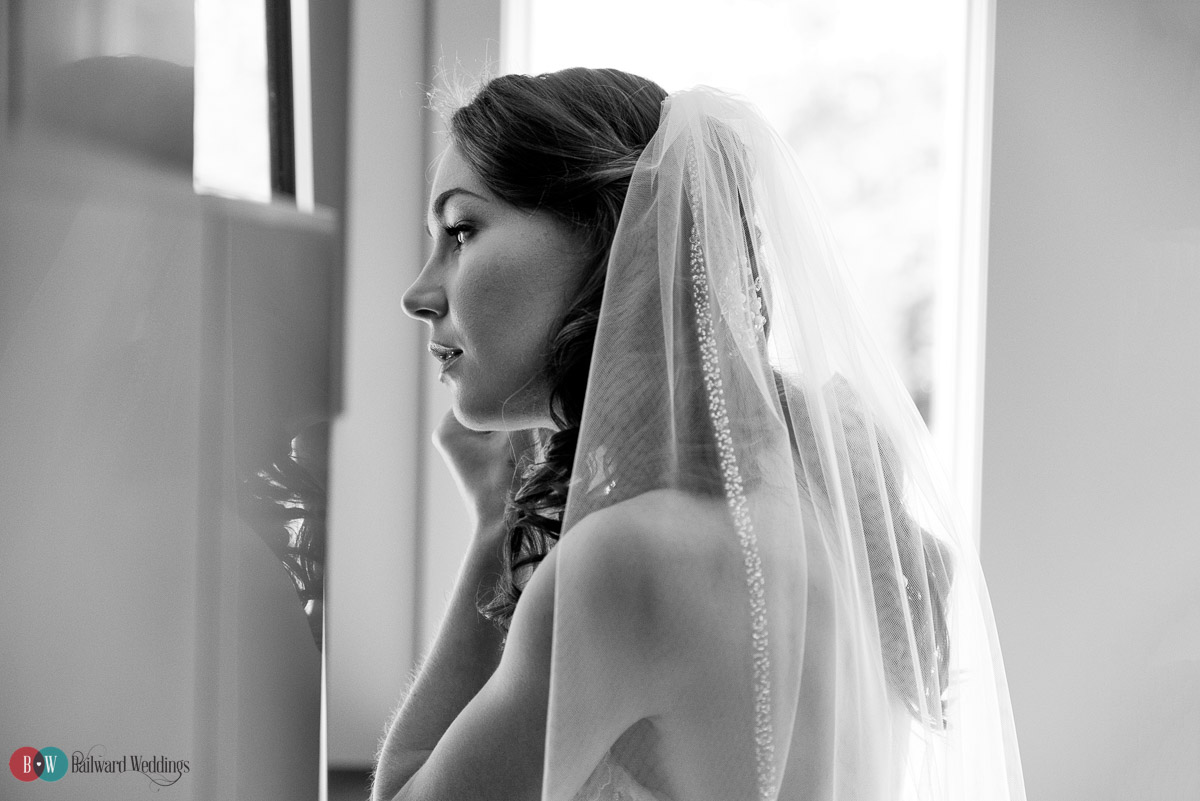 Bride putting on earrings in mirror